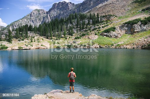 903015102 istock photo Man on an adventure exploring a lake and walking a suspension bridge 903015164