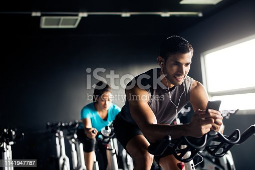 istock Man on an exercise bike holding a cellphone 1141947787