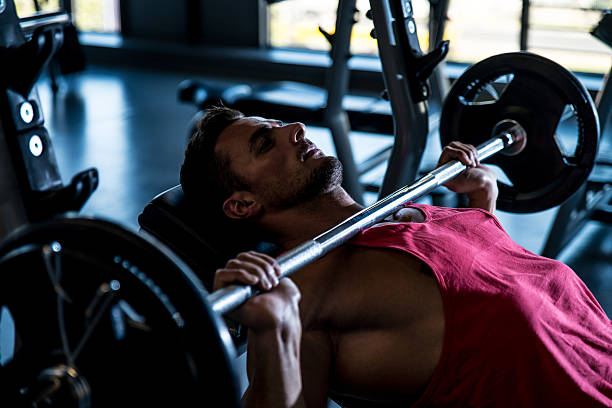 Man on an incline bench doing bench presses stock photo