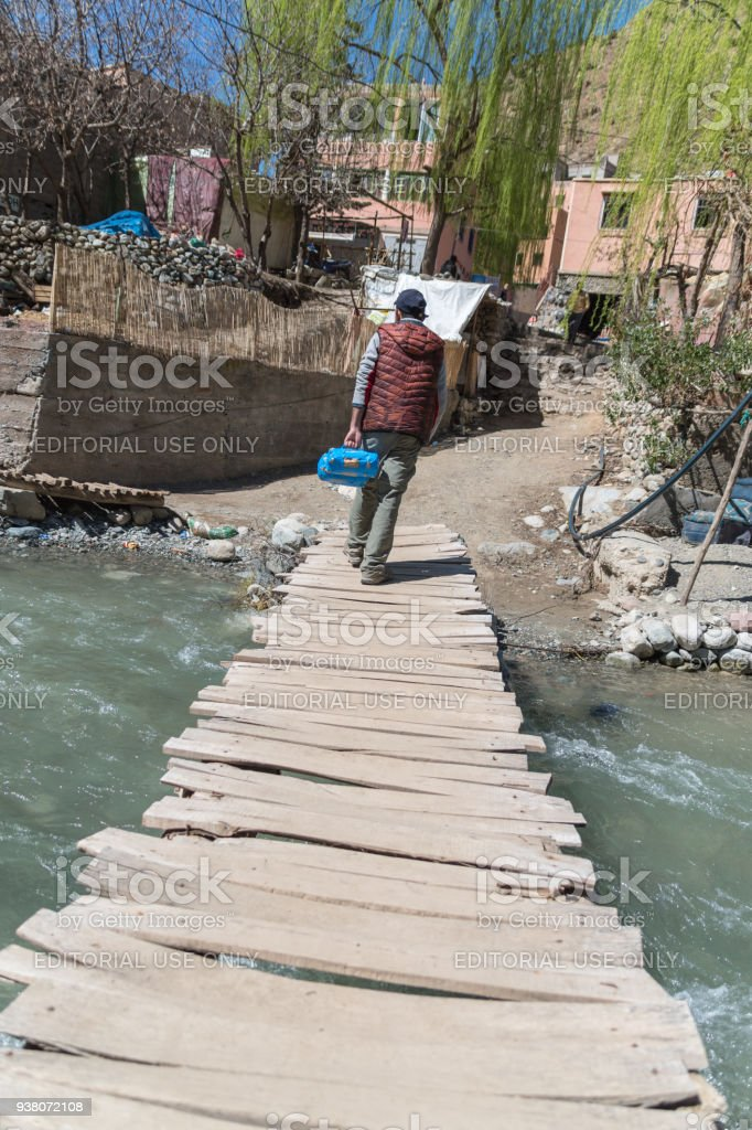 Man on an old wooden bridge over river in High Atlas Mountains, Morocco stock photo