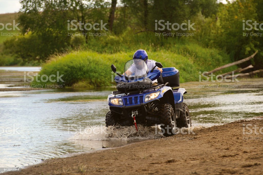 Man on ATV rides on the river, the view from the back. stock photo