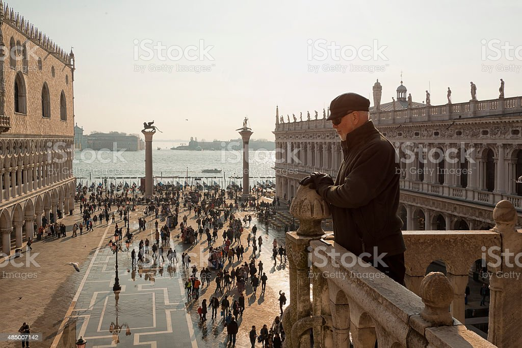 Man on balcony overlooking St Mark's Square, Venice stock photo