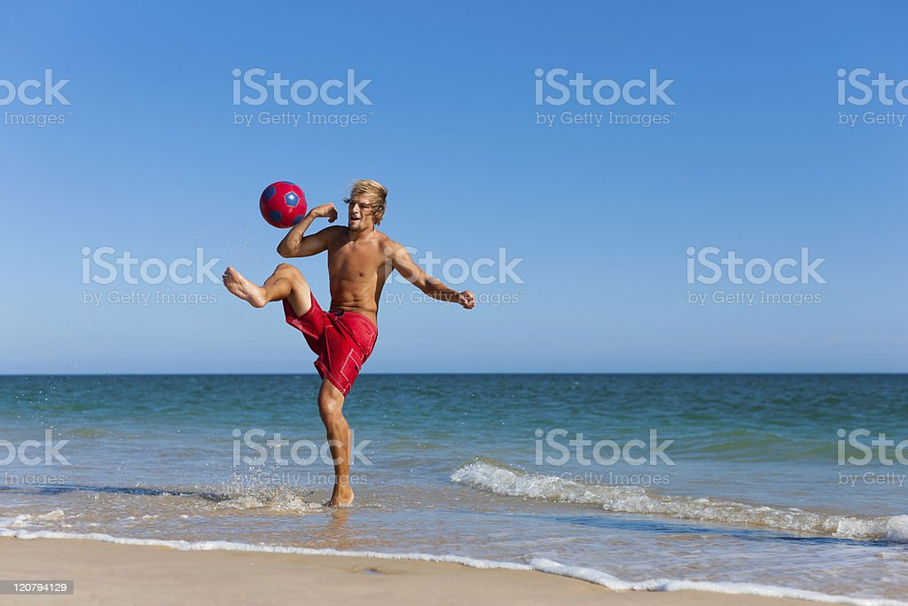 Man on beach playing soccer stock photo