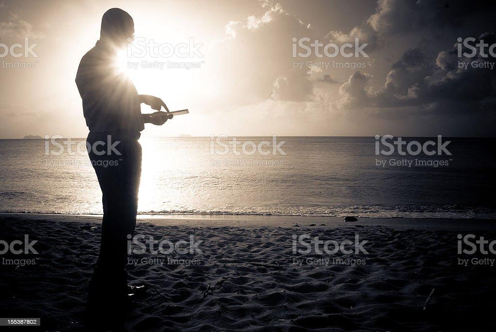 man on beach using digital tablet royalty-free stock photo