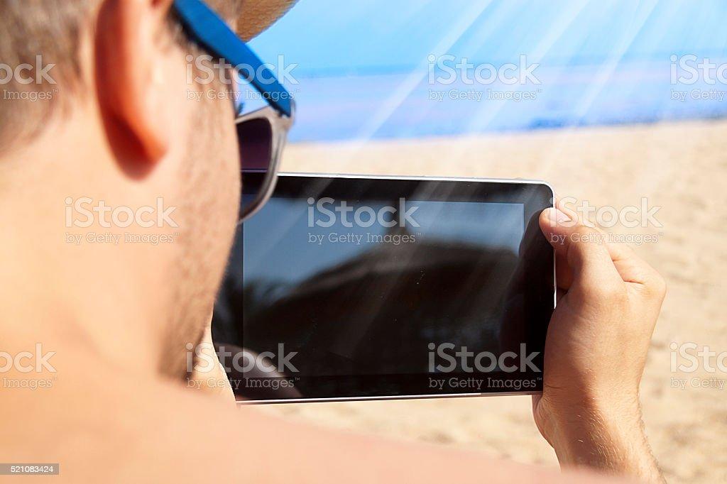 Mężczyzna na plaży z cyfrowy tabletka – zdjęcie
