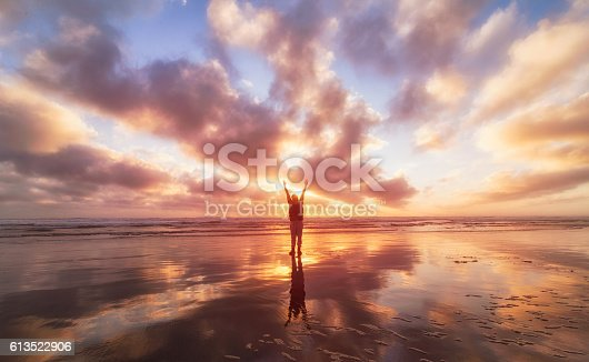 istock Man on beach with over stretched arm. 613522906