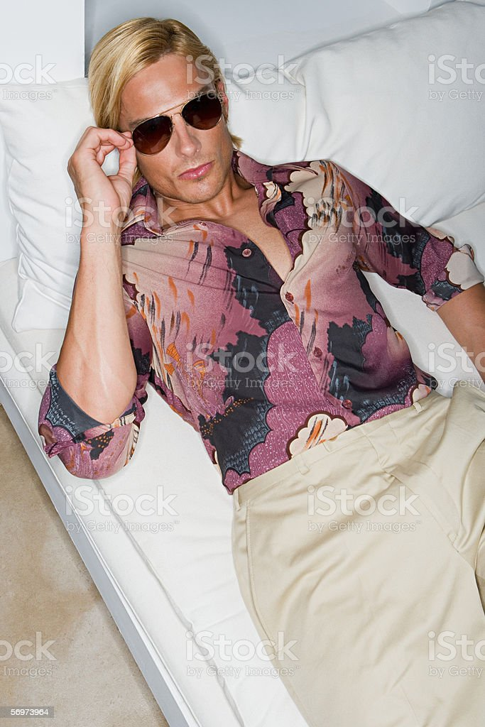 Man on bed wearing sunglasses stock photo