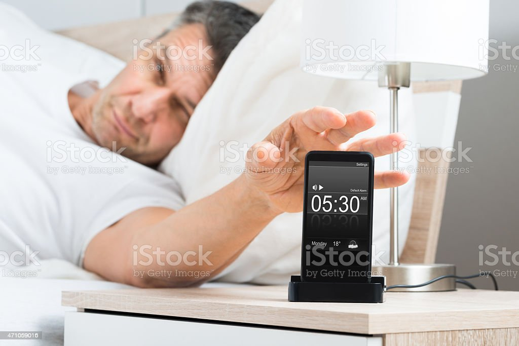 Man On Bed With Cell Phone stock photo