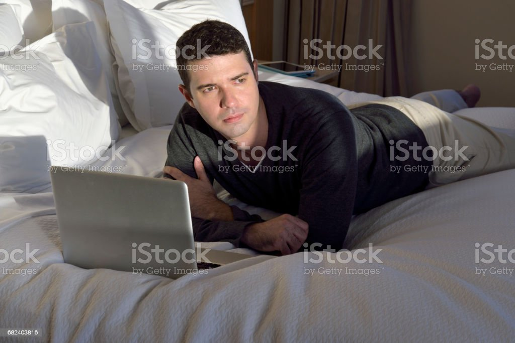 Man on bed with laptop royalty-free stock photo