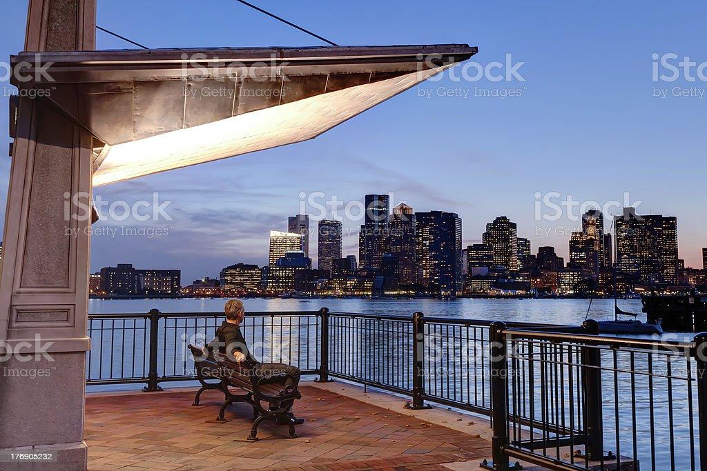 Man on Bench Admiring Boston Skyline at Night stock photo
