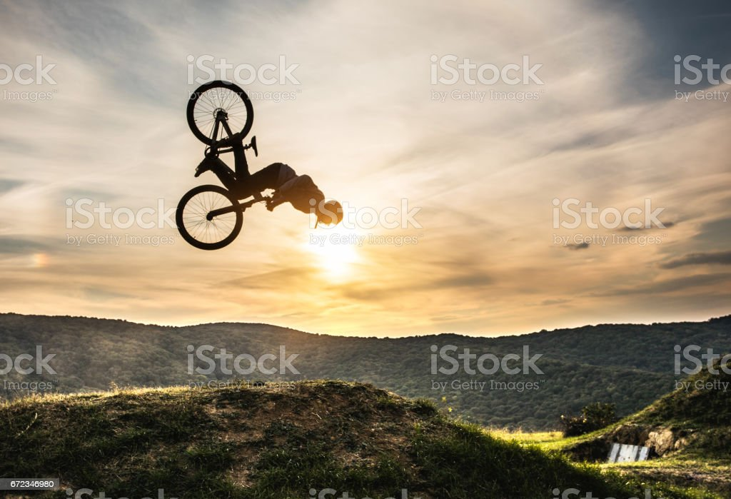 Man on bicycle doing backflip against the sky at sunset. stock photo