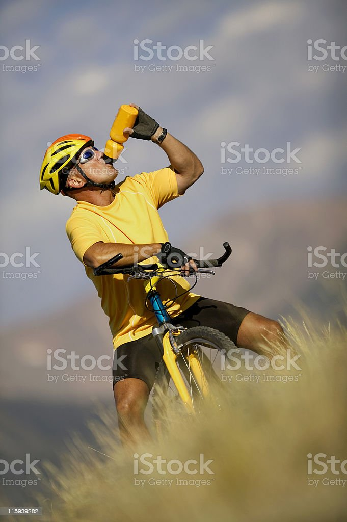 Man on Bicycle Drinking from Water Bottle royalty-free stock photo