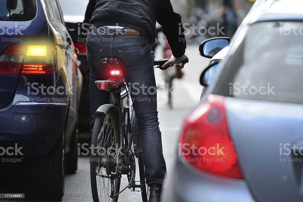 Man on bicycle in traffic stock photo