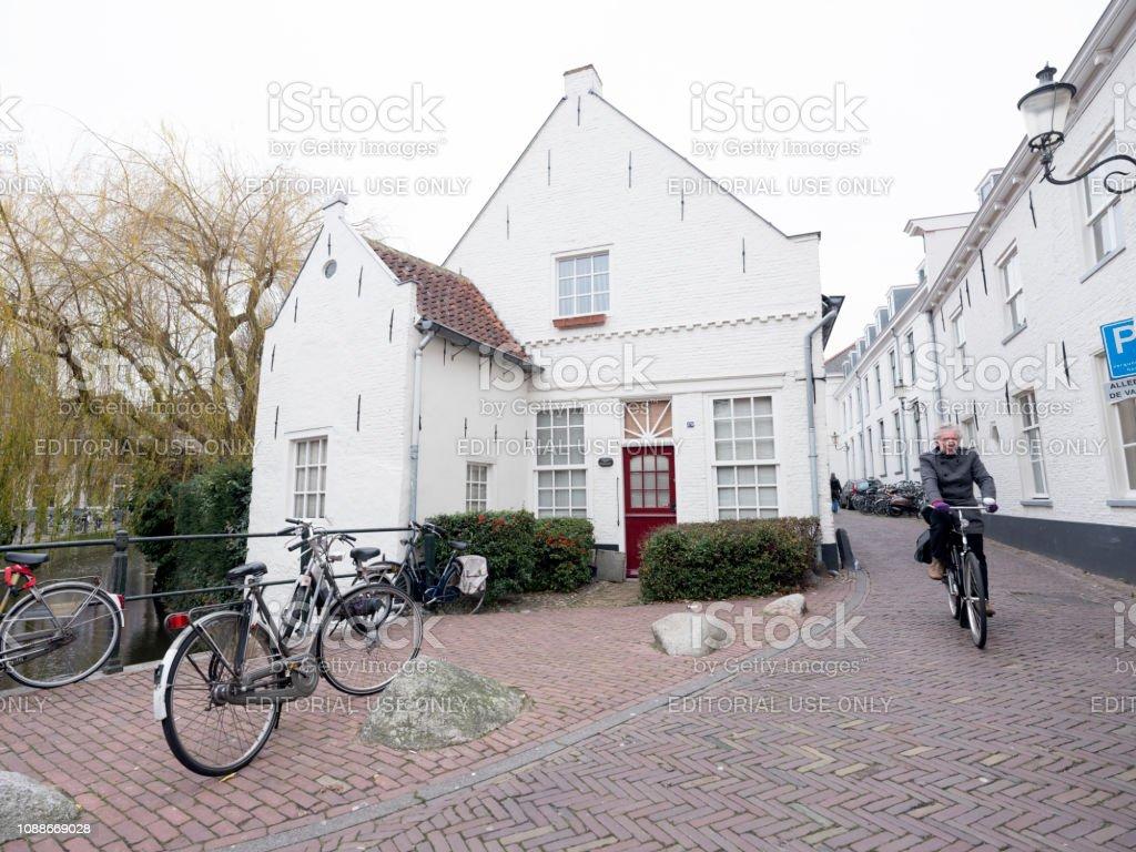 man op fiets passeert andere fietsen in smalle middeleeuwse straat in de stad amersfoort foto
