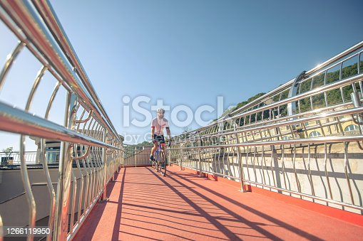 Walk, bridge. Man on bicycle in a sports helmet and clothes riding a bridge in solitude during day