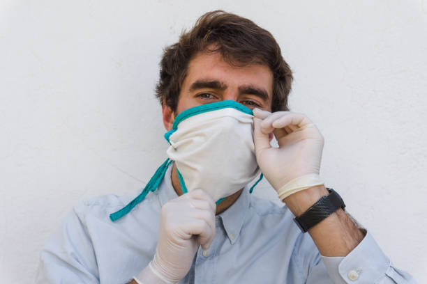 Man on blue shirt puts on a homemade mask with gloves. Coronavirus protection concept. Horizontal portrait. stock photo