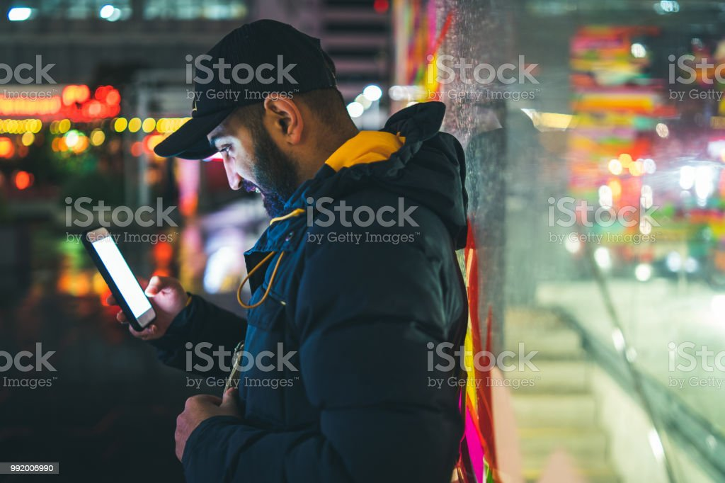 Man on bus stop busy on phone while waiting for bus. stock photo