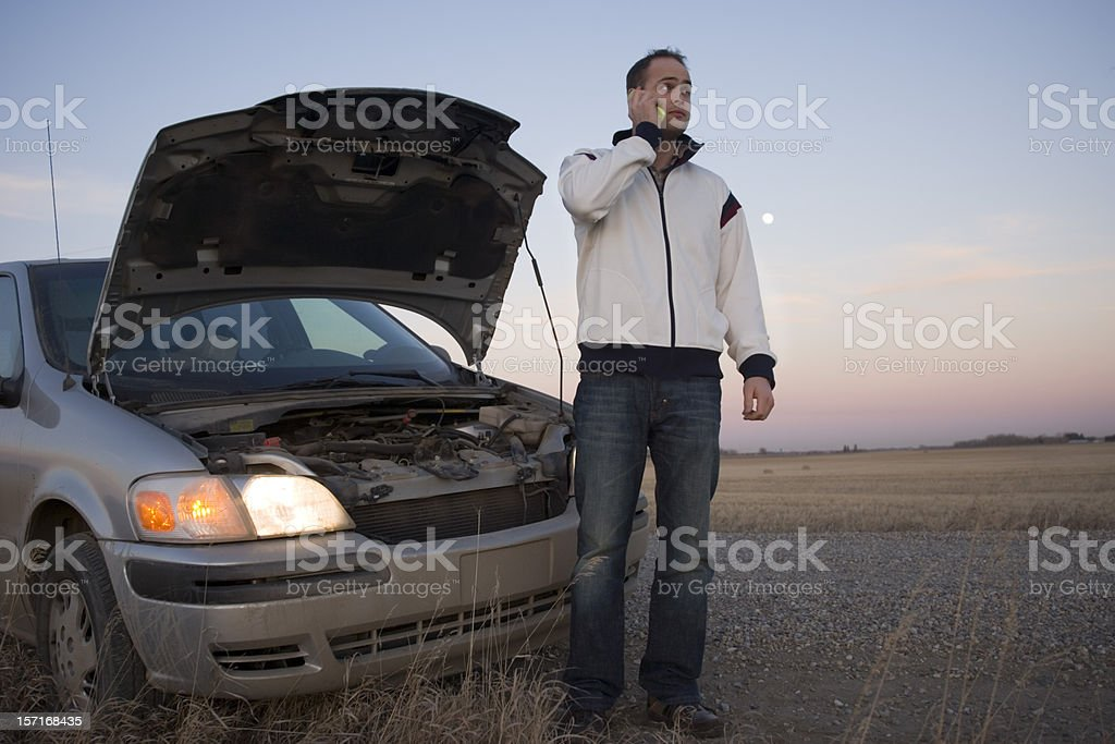 Man on cell phone in front of a broken down van at sunset stock photo