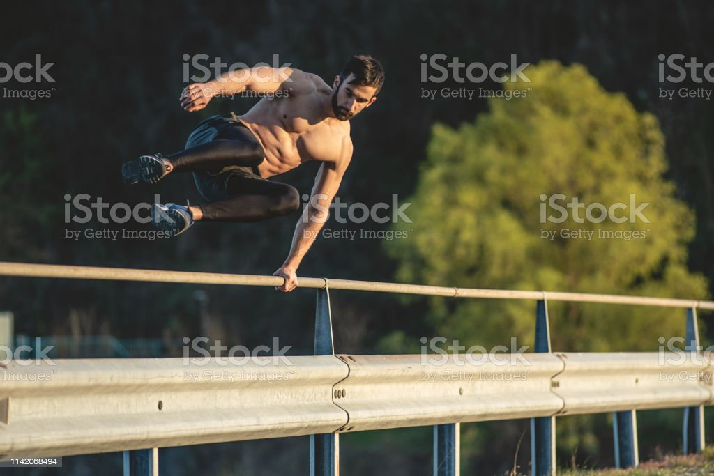 Man on City Streets at the Sunset Doing Parkour Workout