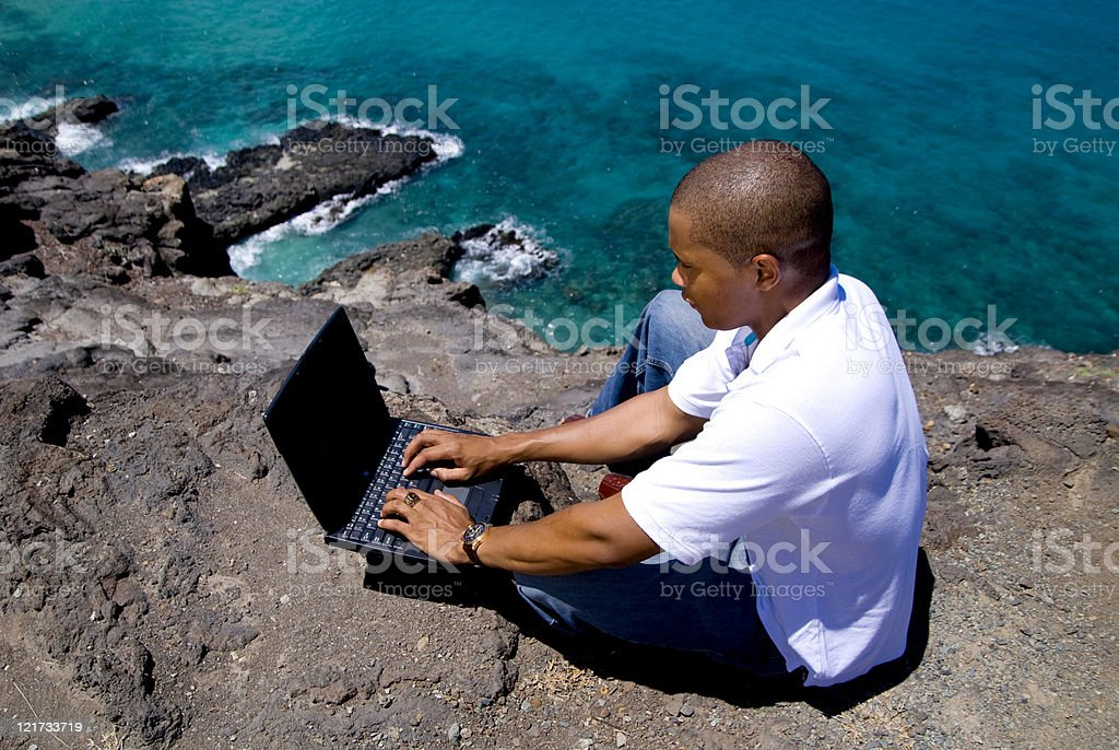 Man On Cliff Using a Laptop royalty-free stock photo