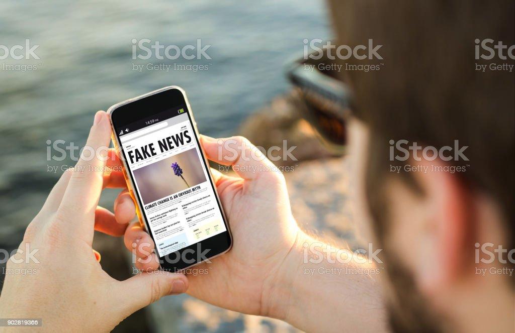 man on coast fake news stock photo