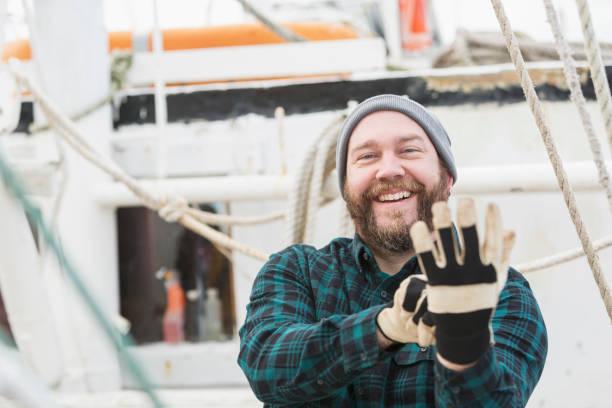 mann auf kommerziellen fischerboot handschuhe anziehen - legere arbeitskleidung stock-fotos und bilder