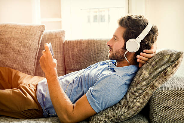 Man on couch watches a movie on mobile phone stock photo