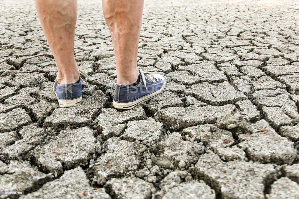 Man on cracked ground stock photo