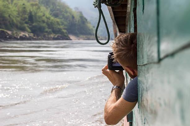 Man on cruise boat in laos taking picture of landscape picture id483485400?b=1&k=6&m=483485400&s=612x612&w=0&h=zcdcuhqch fwqxxcfvef8de0xczw8xwak44e waaatc=