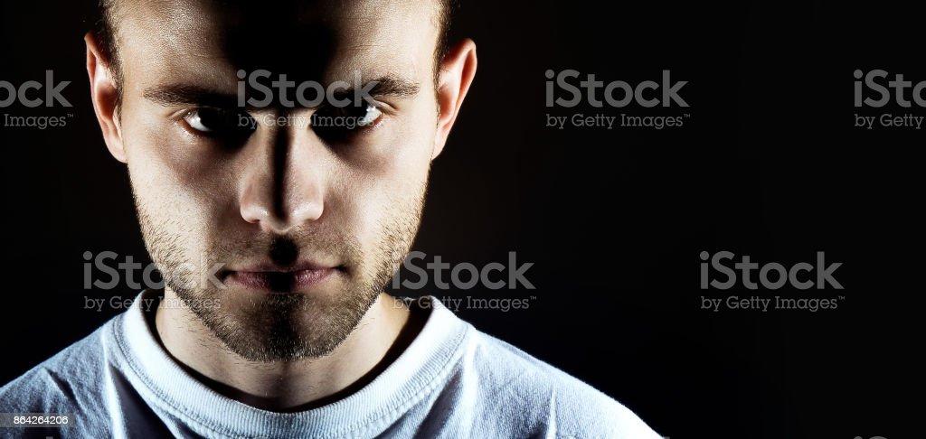 man on dark background looks at camera, dark low key portrait royalty-free stock photo