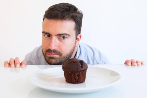 mannen på diet i frestelse av söta muffing - cravings bildbanksfoton och bilder