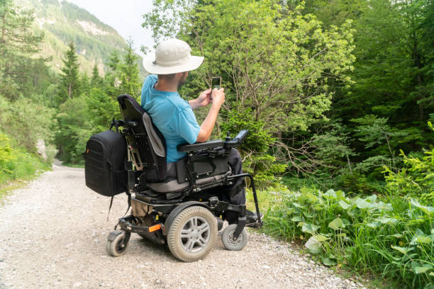man on electric wheelchair using smartphone camera in nature stock photo