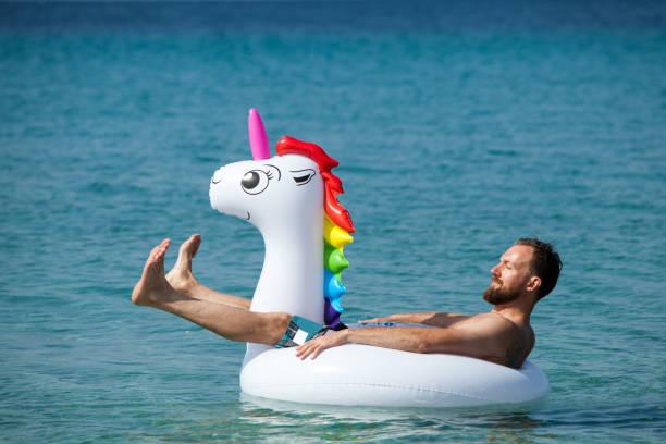 Man on floating unicorn stock photo