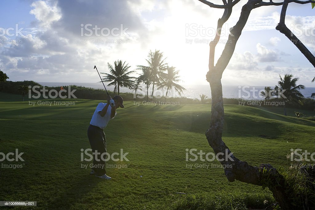 Man on golf course playing golf at dawn royalty-free stock photo