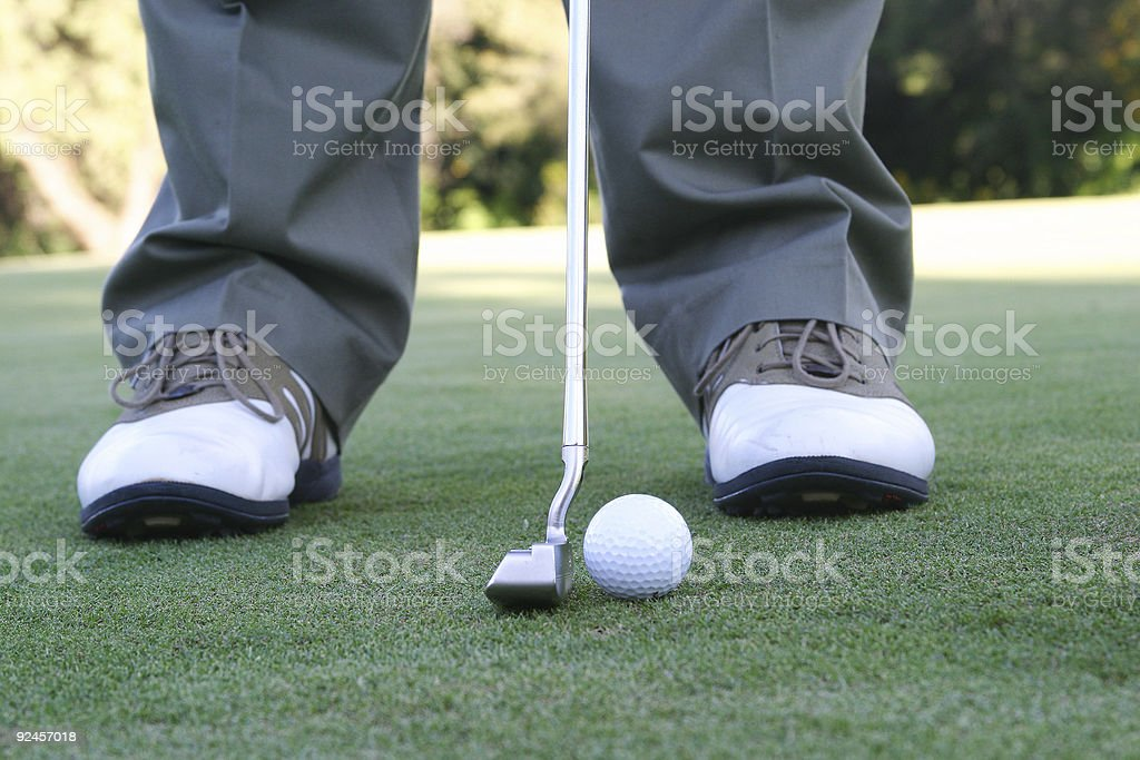 Man on golf green getting ready to put the ball royalty-free stock photo