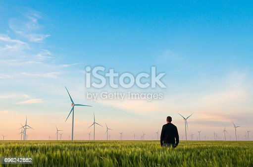 istock Man on green field of wheat with windmills for electric power production 696242882