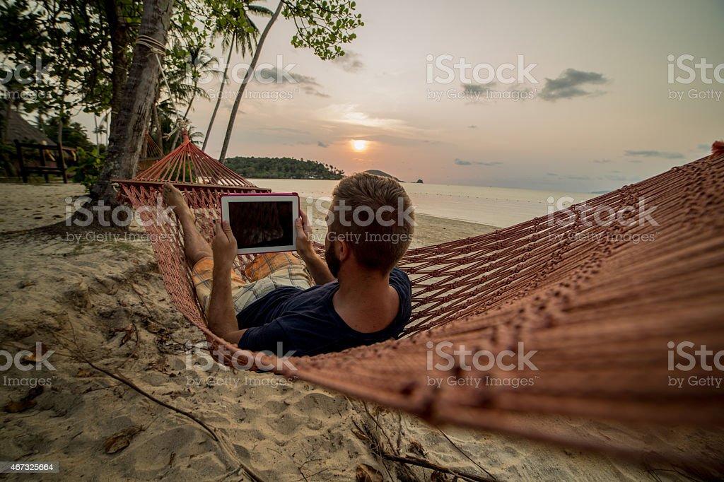 Man on hammock relaxing-Digital tablet stock photo