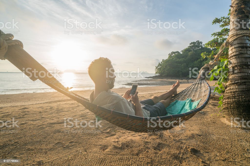 Man on hammock using mobile phone, Thailand stock photo