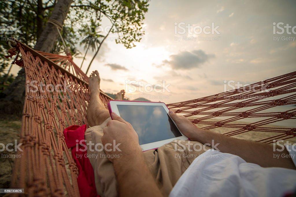 Hombre en una hamaca con tableta digital foto de stock libre de derechos