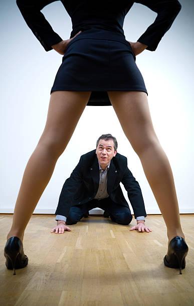 hombre con las manos y las rodillas con mujer de pie por encima de él - piernas abiertas mujer fotografías e imágenes de stock