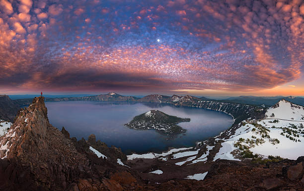 Man on hilltop viewing Crater Lake with full moon stock photo
