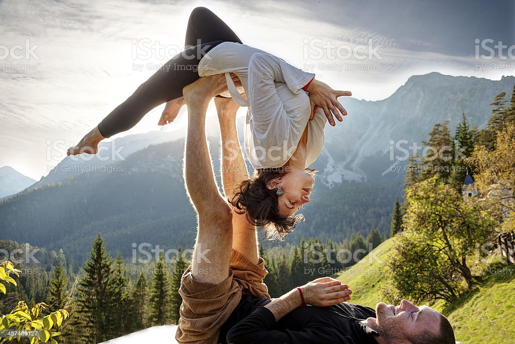 Man on his back balancing a woman laying on his feet stock photo