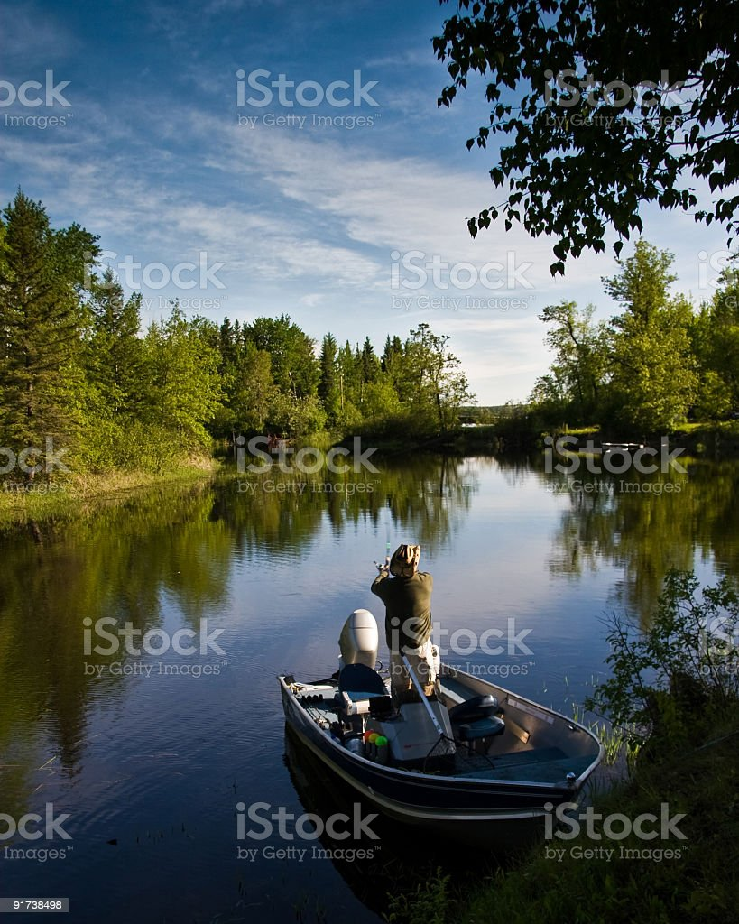 Man on his boat peacefully line fishing in a river royalty-free stock photo