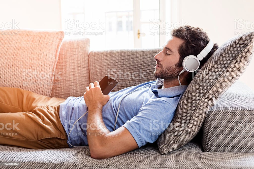Uomo sul suo divano ascoltando musica con uno smartphone - foto stock