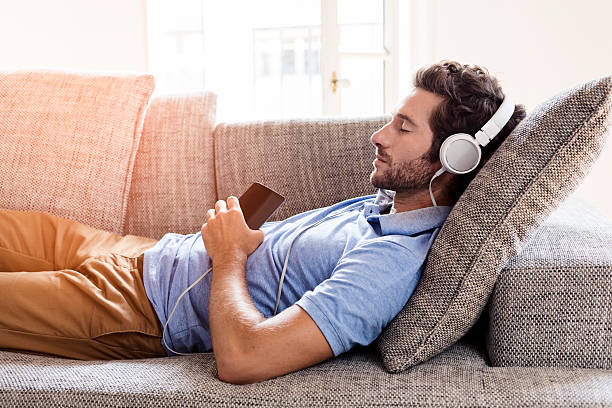 Man on his sofa listening to music with a smartphone stock photo