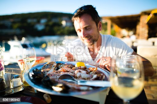 Handsome young man in white t-shirt sitting outside at sunset, eating seafood. Enjoying sunny summer day at seaside.