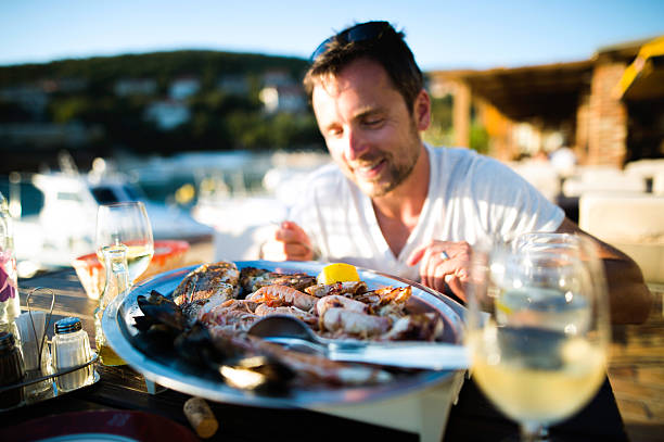 Man on holiday, sitting outside at sunset, eating seafood stock photo