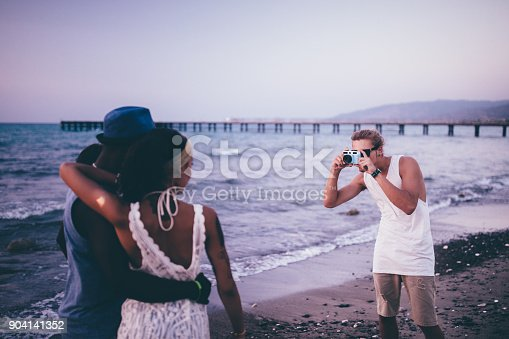 istock Man on holidays photographing friends with vintage camera on beach 904141352