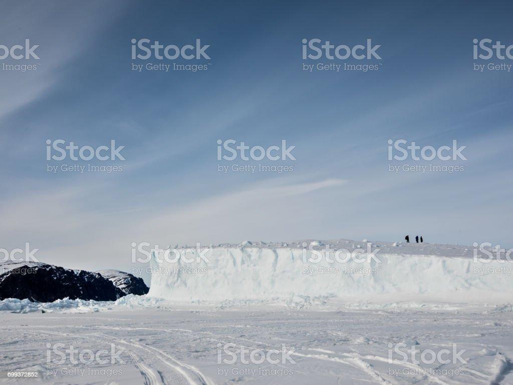 Man on iceberg stuck in Arctic sea ice stock photo