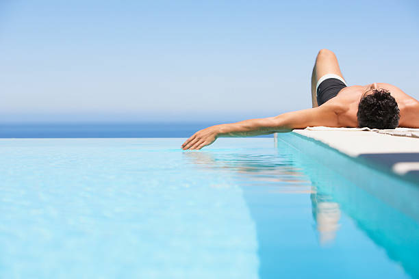 Man on infinity pool deck in swimsuit stock photo